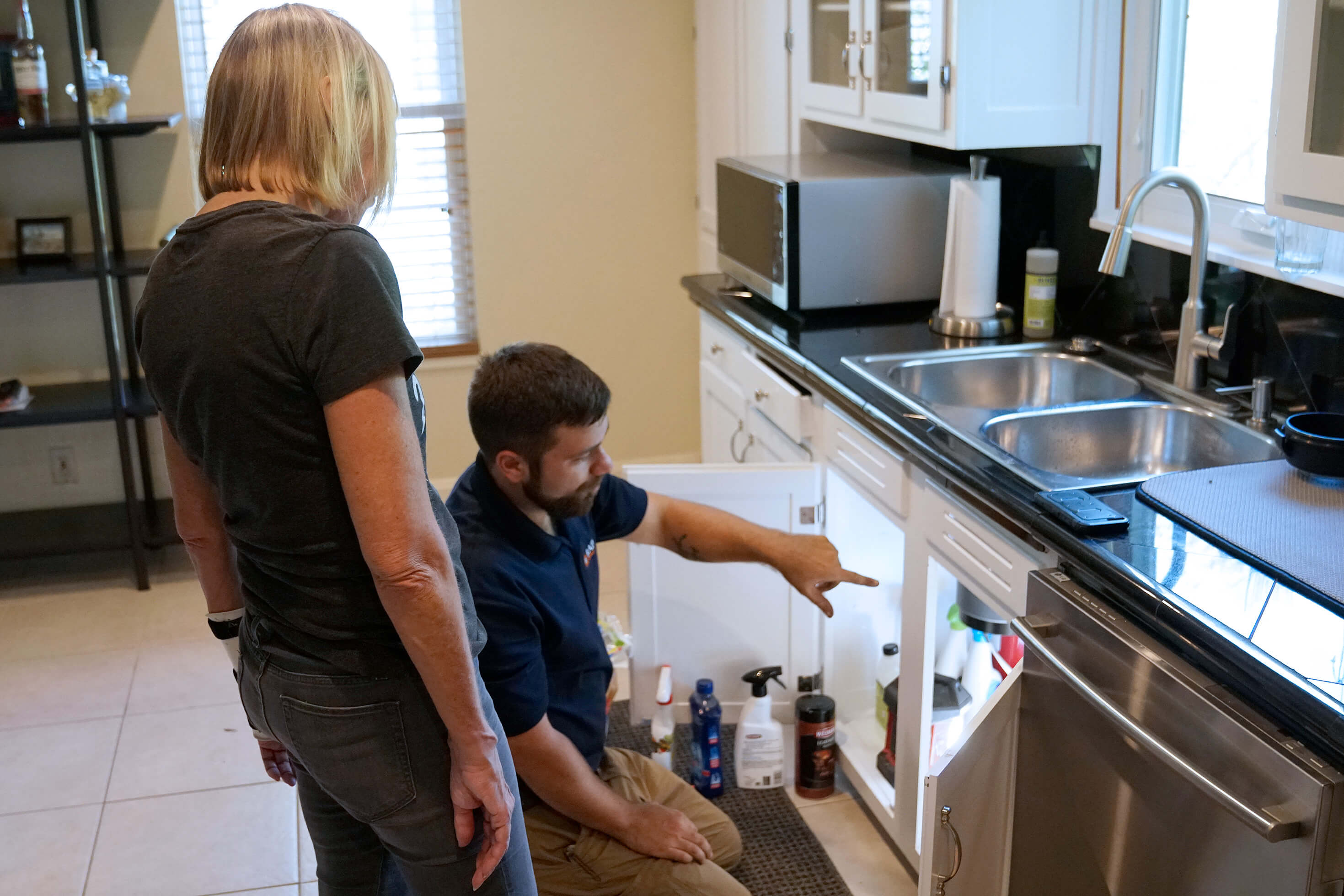 licensed plumber diagnosing problem  with kitchen sink